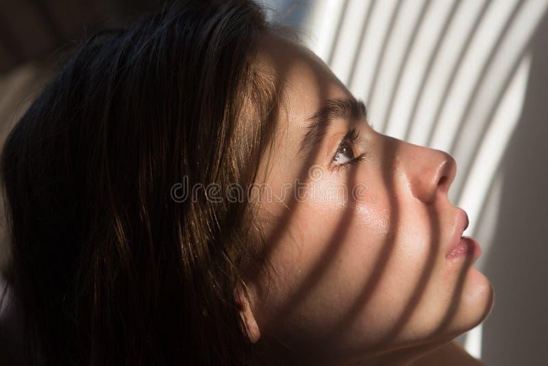 Meisje met licht en schaduw van blinden op jonge gezichtshuid Kuuroordwellness en gezondheid De vrouw met natuurlijke make-up ont stock fotografie