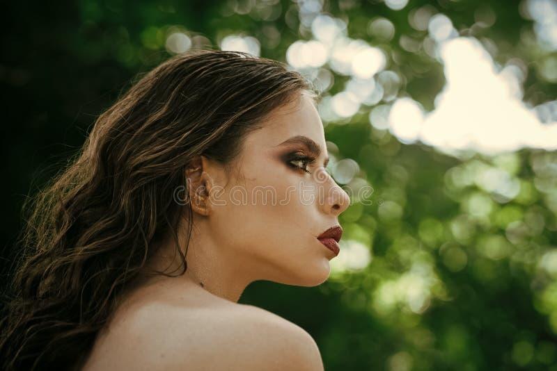 Meisje met make-upgezicht, schoonheid Vrouw met lang donkerbruin haar op aard Vrouw met krullend kapsel en naakte schouder  stock foto's