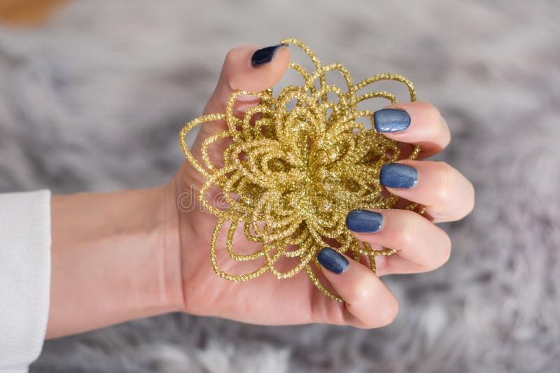 Meisje met marineblauwe manicure die op vingerspijkers decoratieve gouden bloem houden stock afbeelding