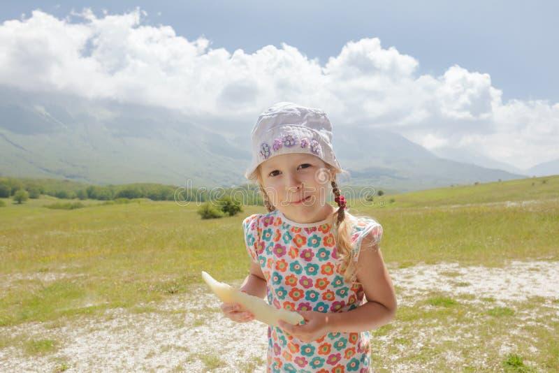Meisje met meloenplak het in hand genieten die op Alpiene weide zijn stock foto's
