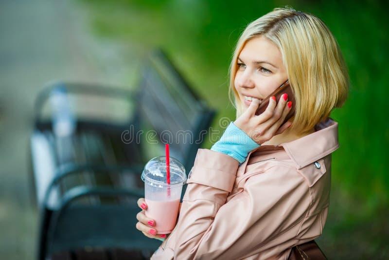 Meisje met milkshake en telefoon royalty-vrije stock afbeelding
