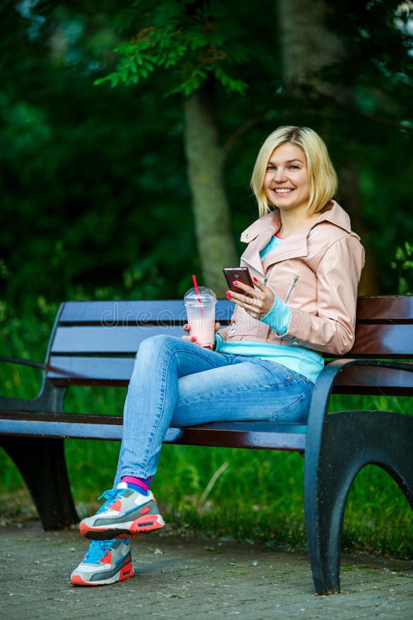 Meisje met milkshake en telefoon stock foto's