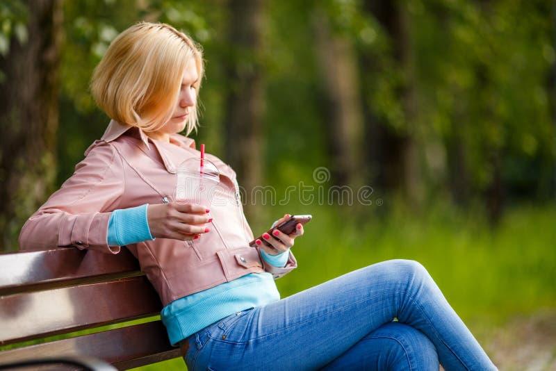 Meisje met milkshake en telefoon royalty-vrije stock foto's