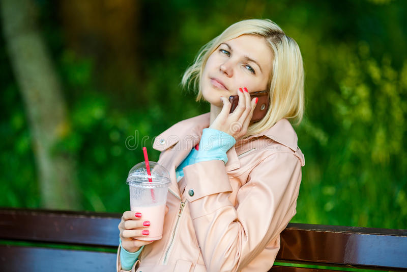 Meisje met milkshake en telefoon royalty-vrije stock fotografie