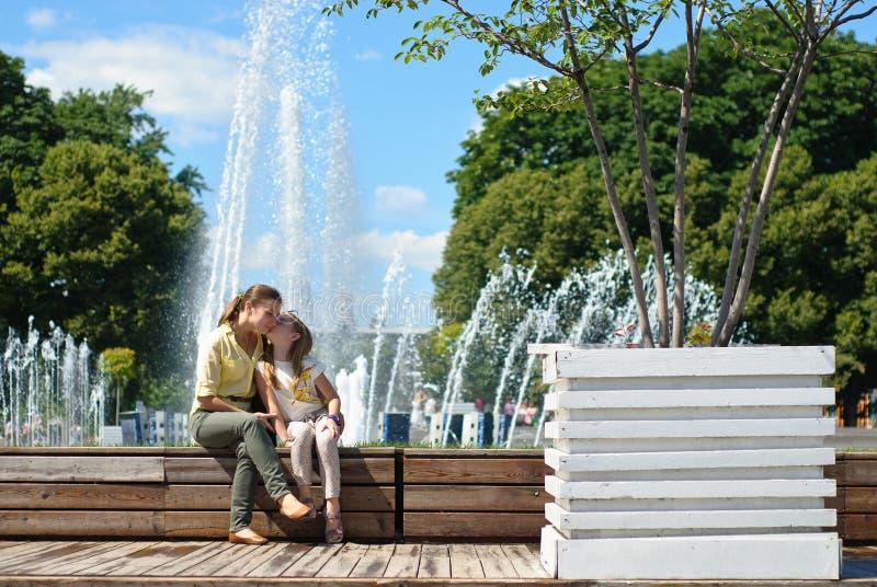 Meisje met moeder die in het park koesteren royalty-vrije stock afbeeldingen