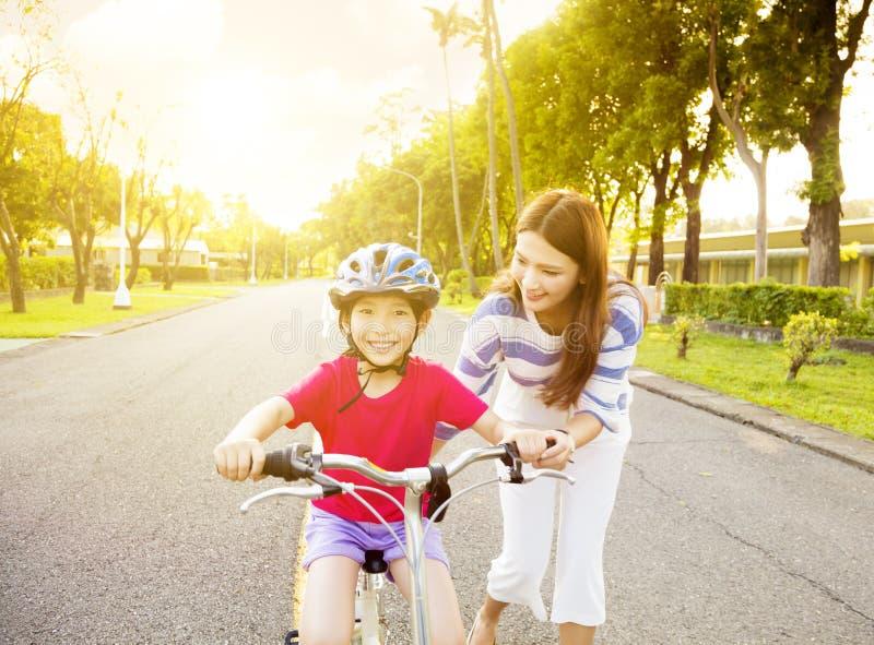 meisje met moederpraktijk aan het berijden van fiets stock foto's