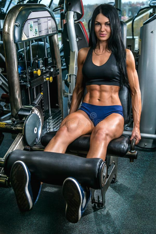Meisje met mooi atletisch lichaam die oefeningen voor benen in opleidingsaparatus doen royalty-vrije stock foto
