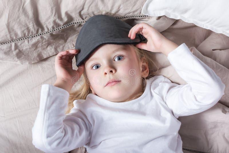 Meisje met mooie ogen die in bed liggen Het kind verwijdert het slaapmasker royalty-vrije stock afbeelding