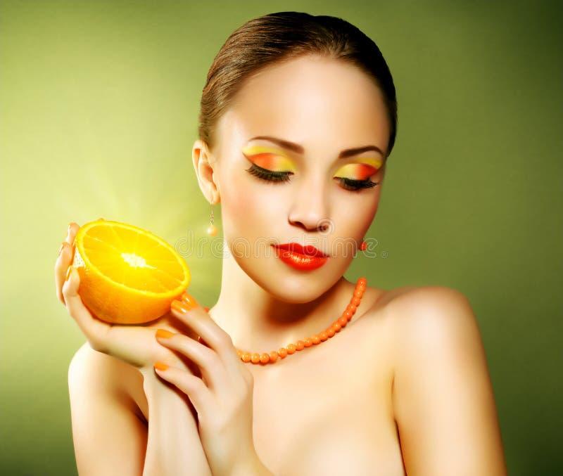 Meisje met mooie samenstelling die oranje fruit houden stock afbeelding