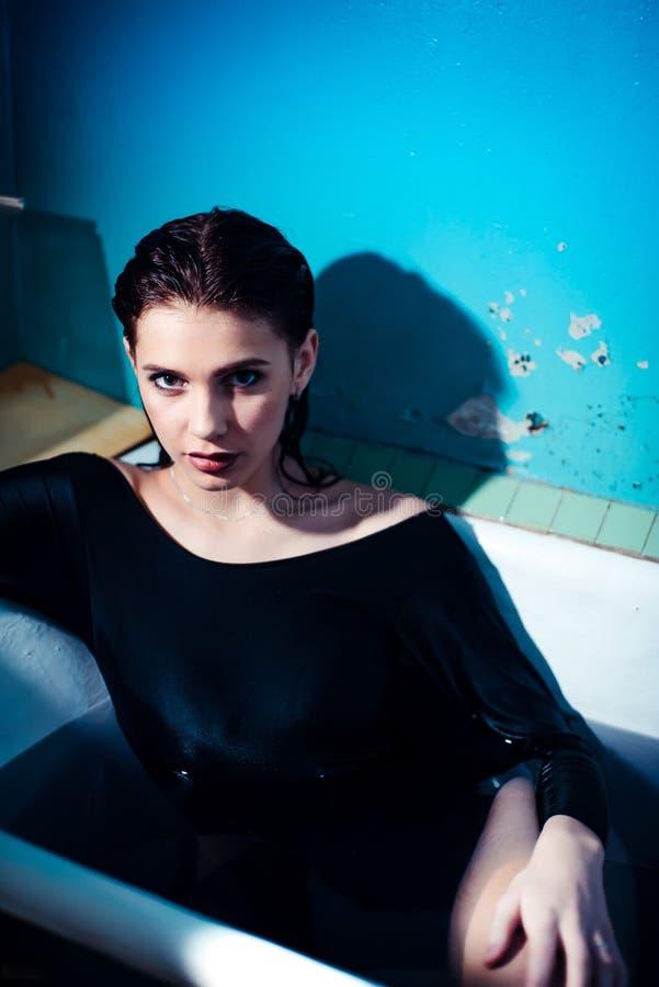 Meisje met naakte schouders die in de badkamers met gekleurd purper water liggen Het concept van de manier stock afbeeldingen