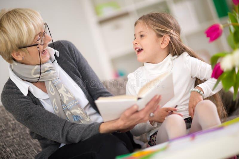 Meisje met oma die geinteresseerd boek lezen royalty-vrije stock foto's