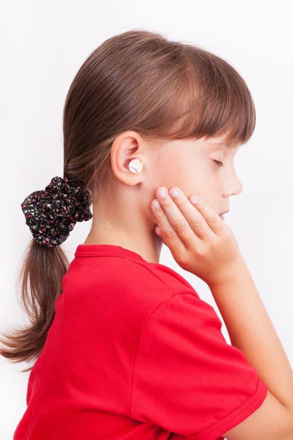 Meisje met oorstoppen in uw oren stock afbeelding
