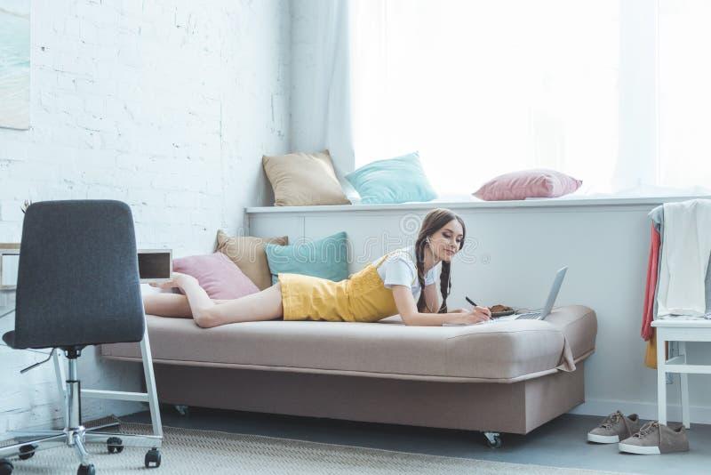 meisje met oortelefoons en laptop die in voorbeeldenboek schrijven royalty-vrije stock afbeelding