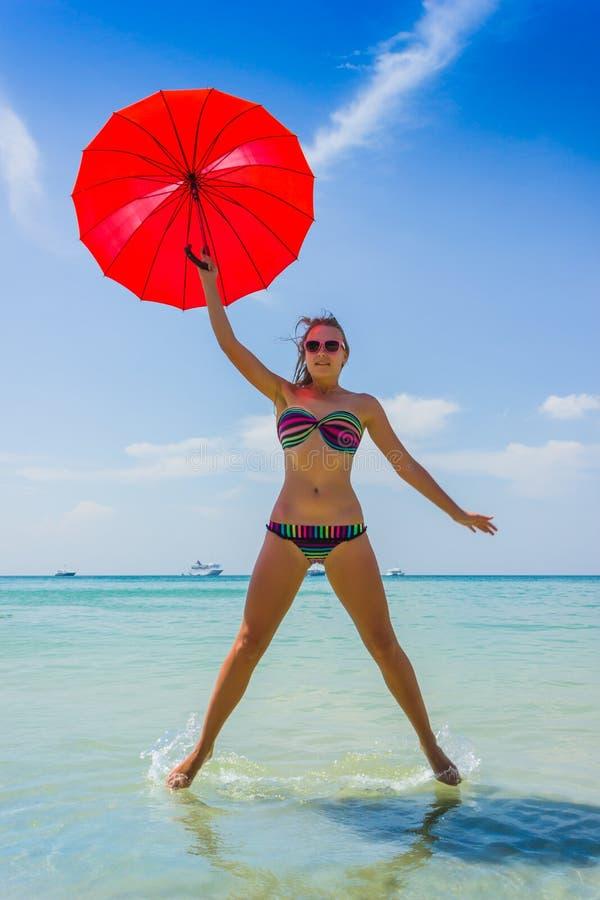 Meisje met oranje paraplu op het strand in Thailand stock fotografie