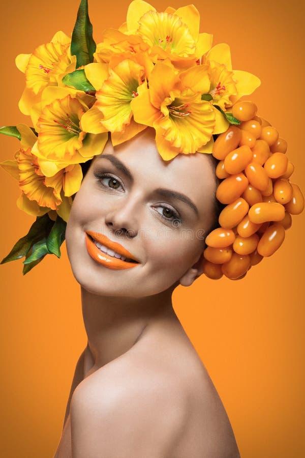 Meisje met oranje tomaten en bloemen stock afbeeldingen