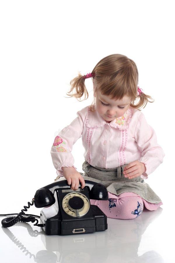 Meisje met oude zwarte telefoon. stock afbeeldingen