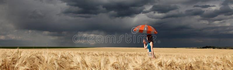 Meisje met paraplu bij gebied. in onweer stock foto's