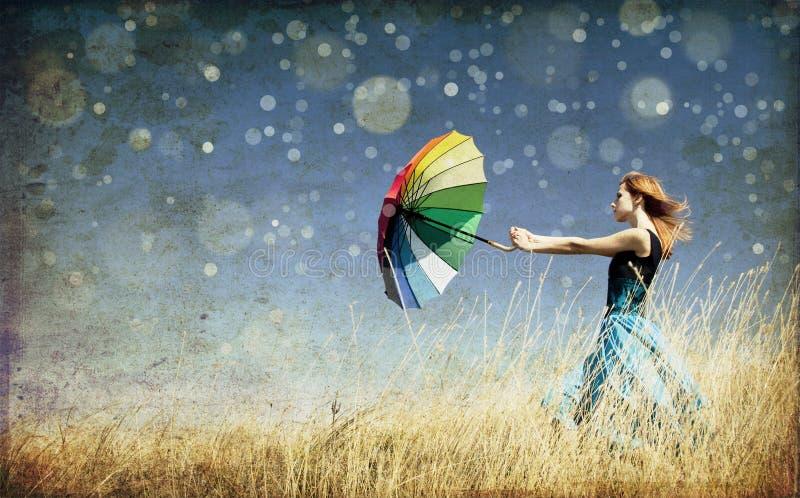 Meisje met paraplu bij winderig gras stock afbeeldingen
