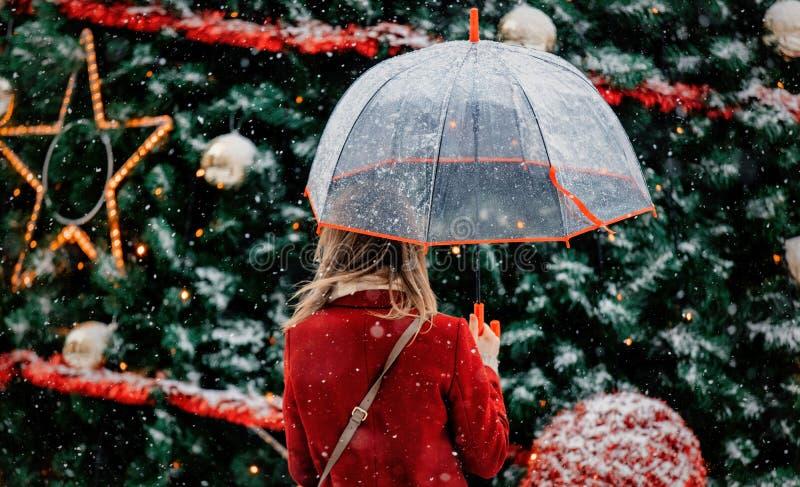 Meisje met paraplu dichtbij Kerstboom stock afbeeldingen