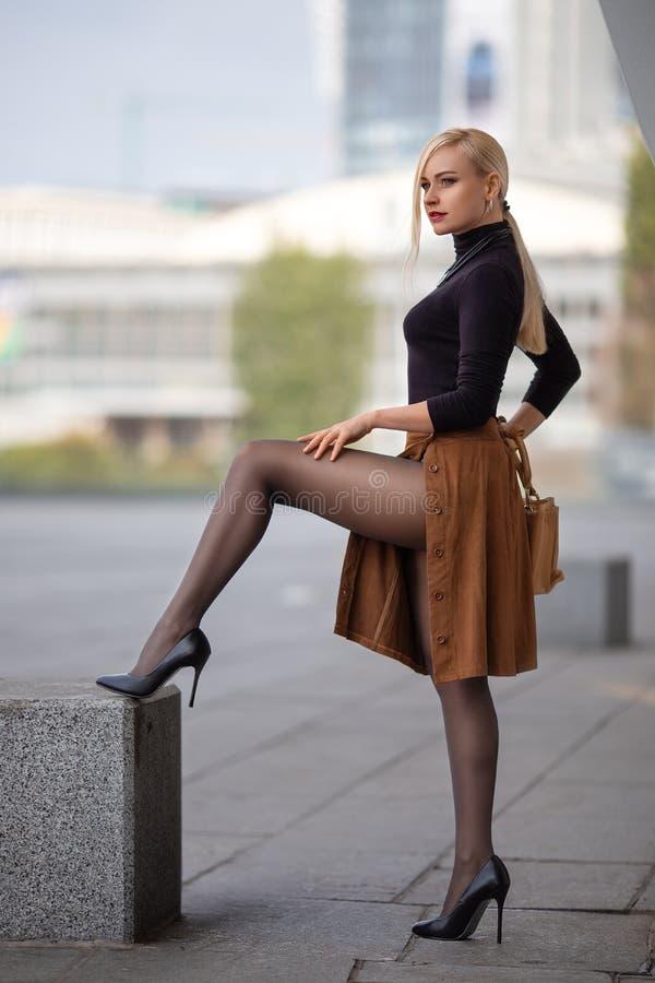 Meisje met perfecte benen in nylonkousen bij het stadsvierkant stock foto's