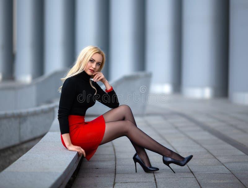 Meisje met perfecte benen in nylonkousen bij het stadsvierkant stock afbeelding