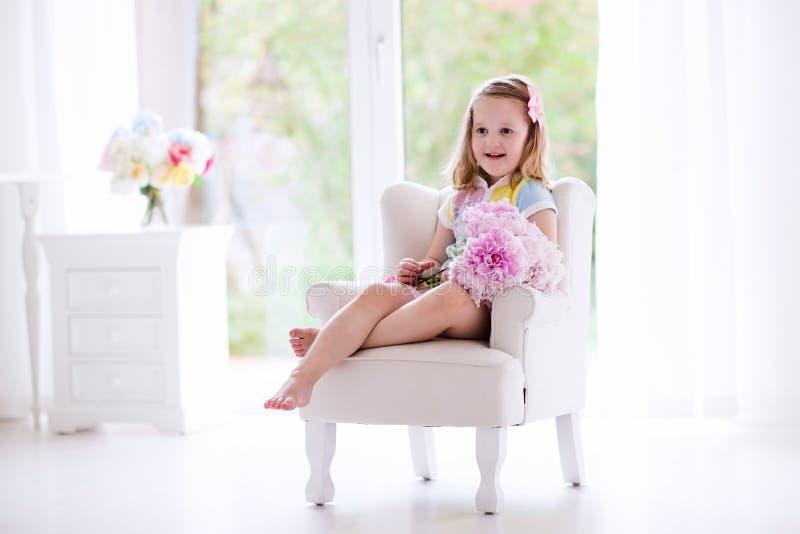 Meisje met pioenbloemen in witte slaapkamer stock foto's
