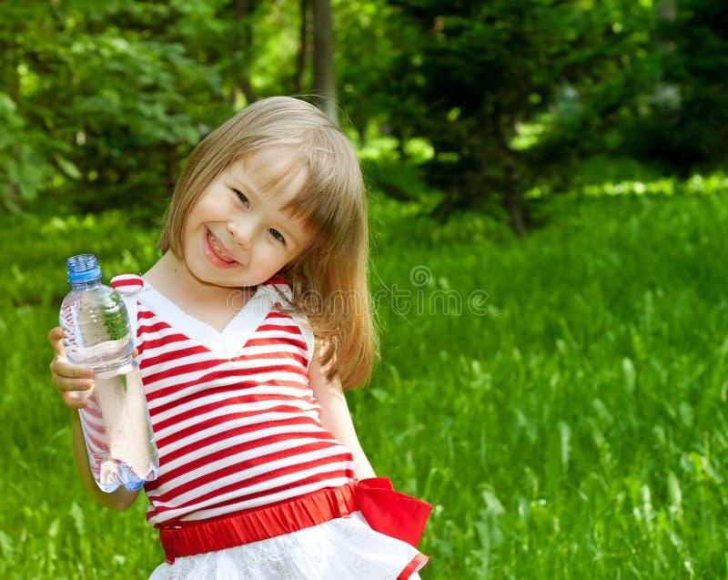 Meisje met plastic fles mineraalwater stock afbeelding