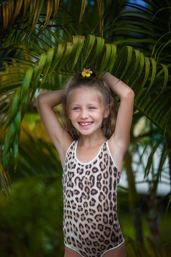 Meisje met plumeriabloem in haar haar tegen de achtergrond van palmen royalty-vrije stock afbeelding