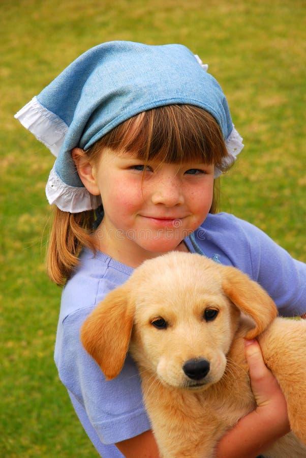 Meisje met puppyhuisdier stock foto