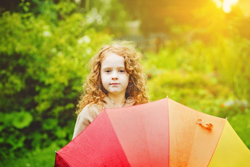 Meisje met regenboogparaplu, onder zonneschijn royalty-vrije stock foto's