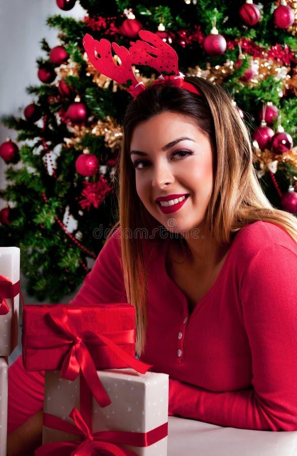 Meisje met rendierhoornen op hoofd en rode sweater en giftdozen, Kerstboom op achtergrond stock afbeeldingen