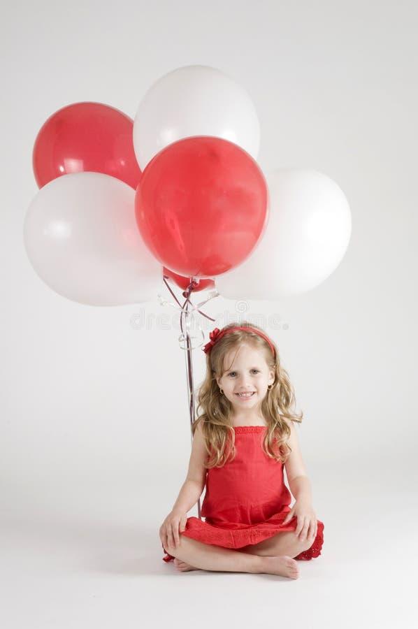 Meisje met rode en witte ballons royalty-vrije stock afbeelding