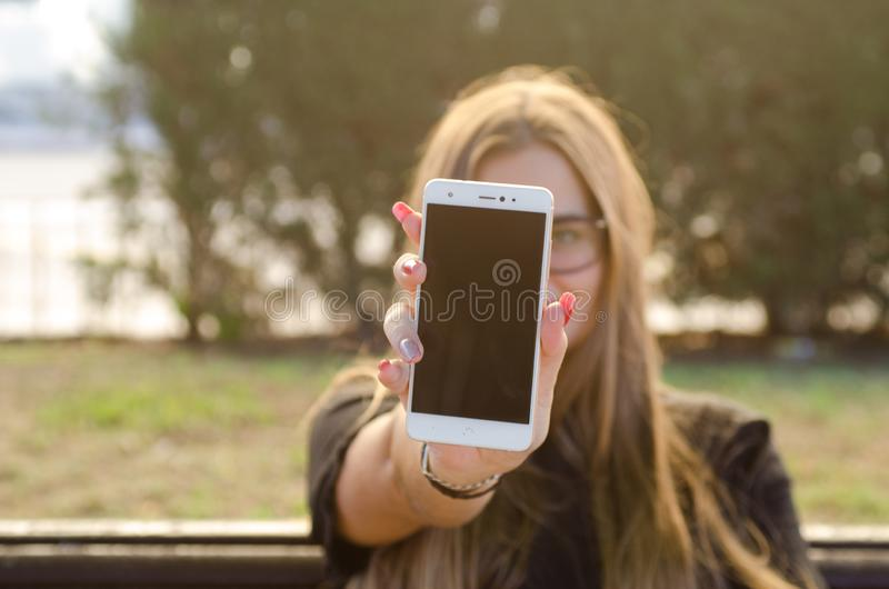 Meisje met rode spijkers, die witte smartphone met het zwarte scherm tonen stock fotografie