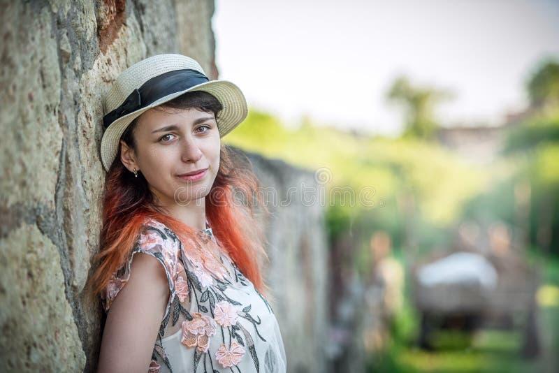 Meisje met rood haar in een hoed die terug tegen een steen retro w leunen royalty-vrije stock foto's