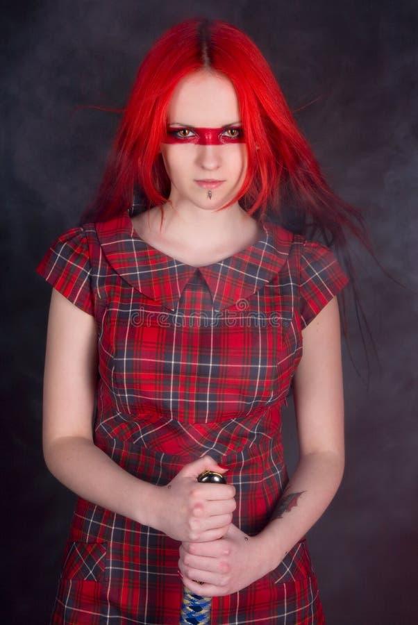 Meisje met rood haar en een zwaard stock foto's