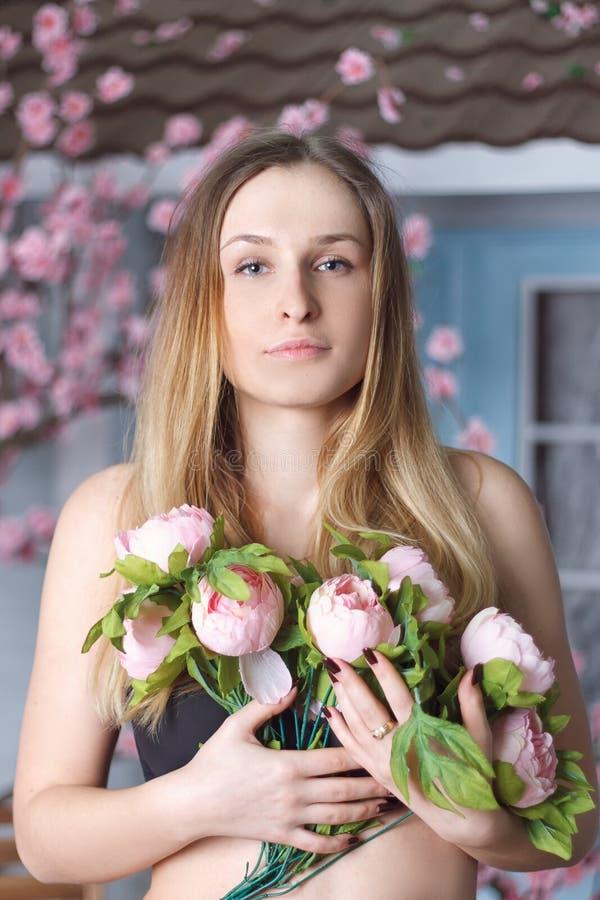 Meisje met roze pioenenboeket stock foto's