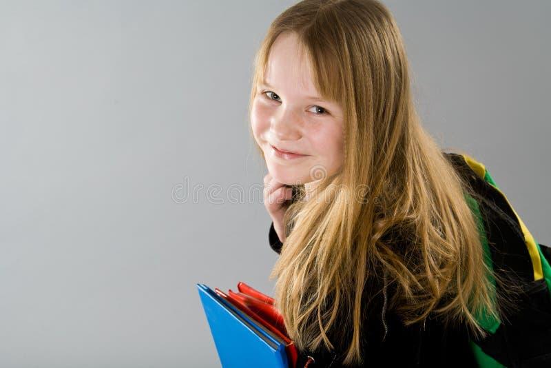 Meisje met rugzak en boeken stock foto