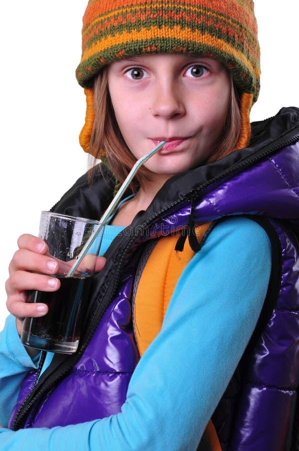 Meisje met rugzak en hoeden het drinken kola over wit wordt geïsoleerd dat stock afbeelding