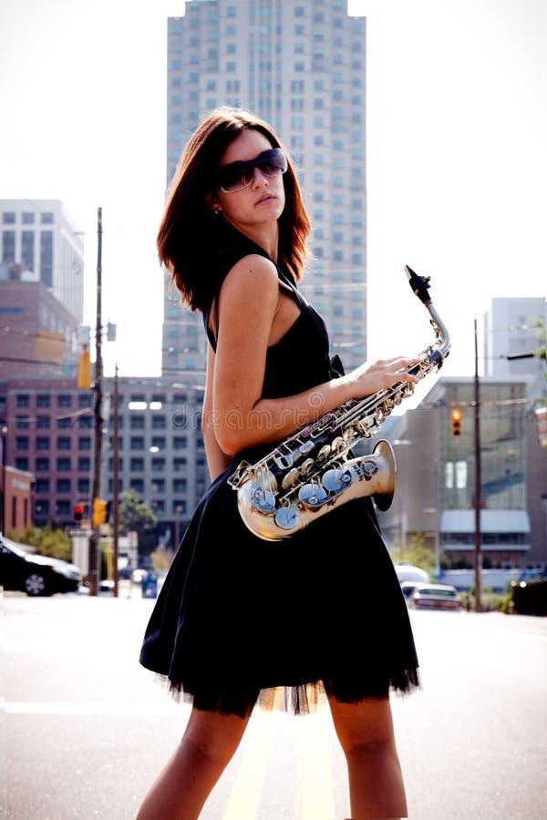 Meisje met Saxofoon in Straat stock foto's