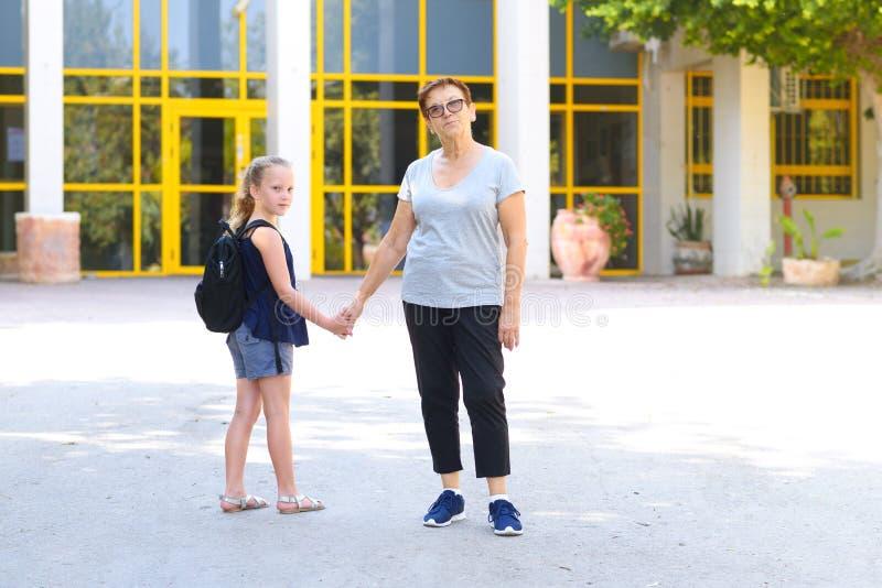 Meisje met schooltas of schooltas die aan school met grootmoeder lopen royalty-vrije stock afbeeldingen