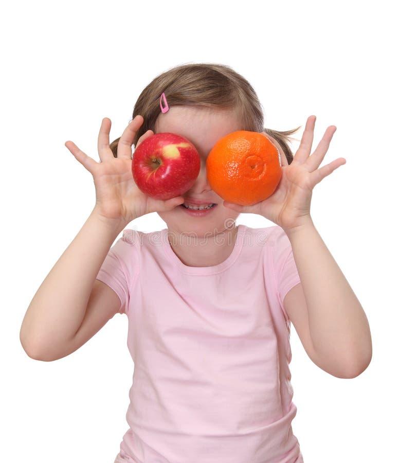 Meisje met sinaasappel en appel stock afbeeldingen