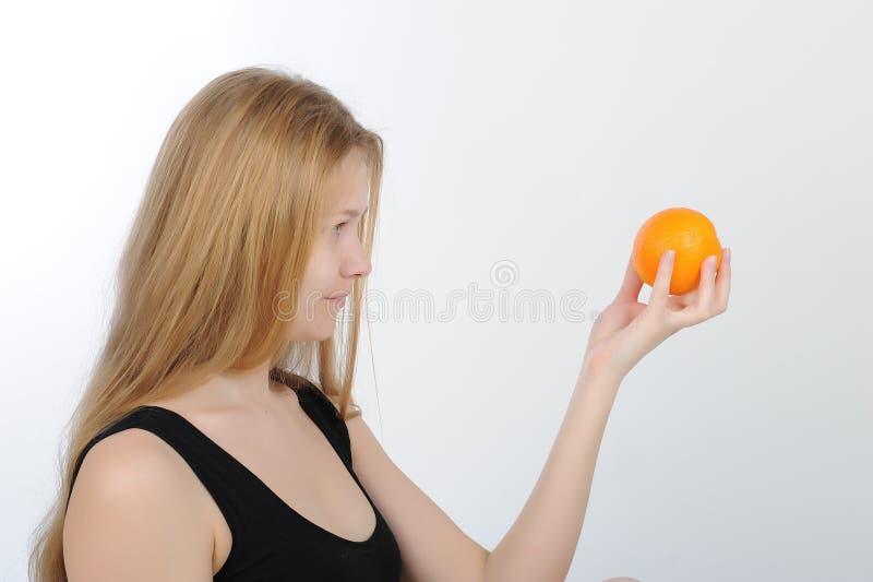 Meisje met sinaasappel in haar handen royalty-vrije stock afbeelding