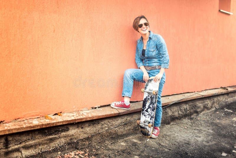 Meisje met skateboard en zonnebril die een stedelijke levensstijl leven Hipsterconcept met jong vrouw en skateboard, instagram fi royalty-vrije stock afbeelding