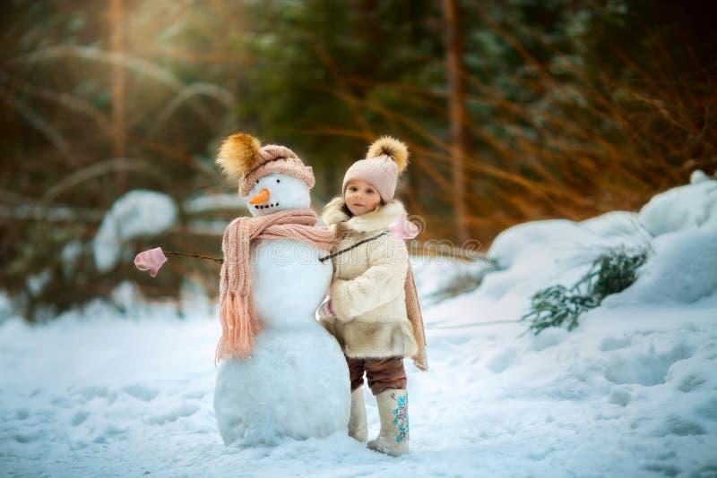Meisje met sneeuwman stock afbeeldingen