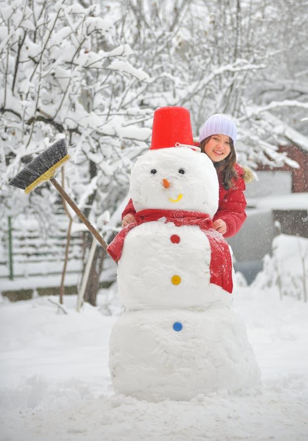 Meisje met sneeuwman stock afbeelding