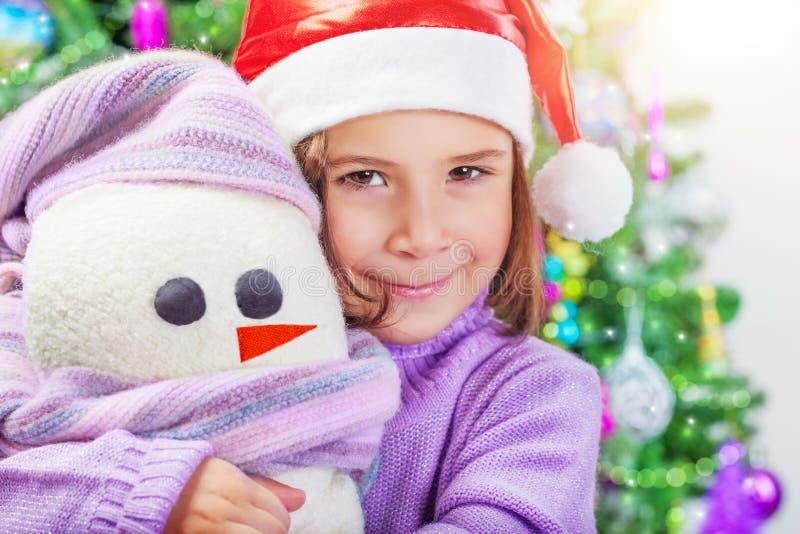 Meisje met sneeuwmanstuk speelgoed stock foto's