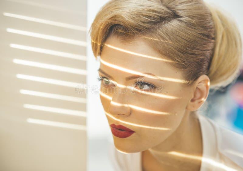 Meisje met stroken van licht en schaduwen op haar gezicht stock fotografie