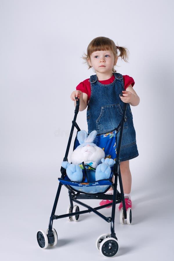 Meisje met stuk speelgoed konijn in kinderwagen royalty-vrije stock fotografie