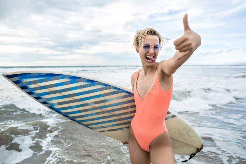 Meisje met surfplank op strand stock afbeelding