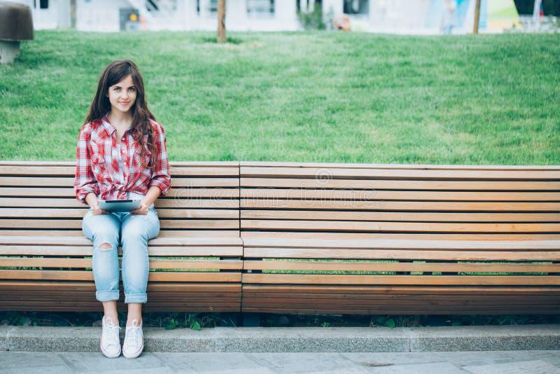 Meisje met tabletzitting op de bank royalty-vrije stock fotografie